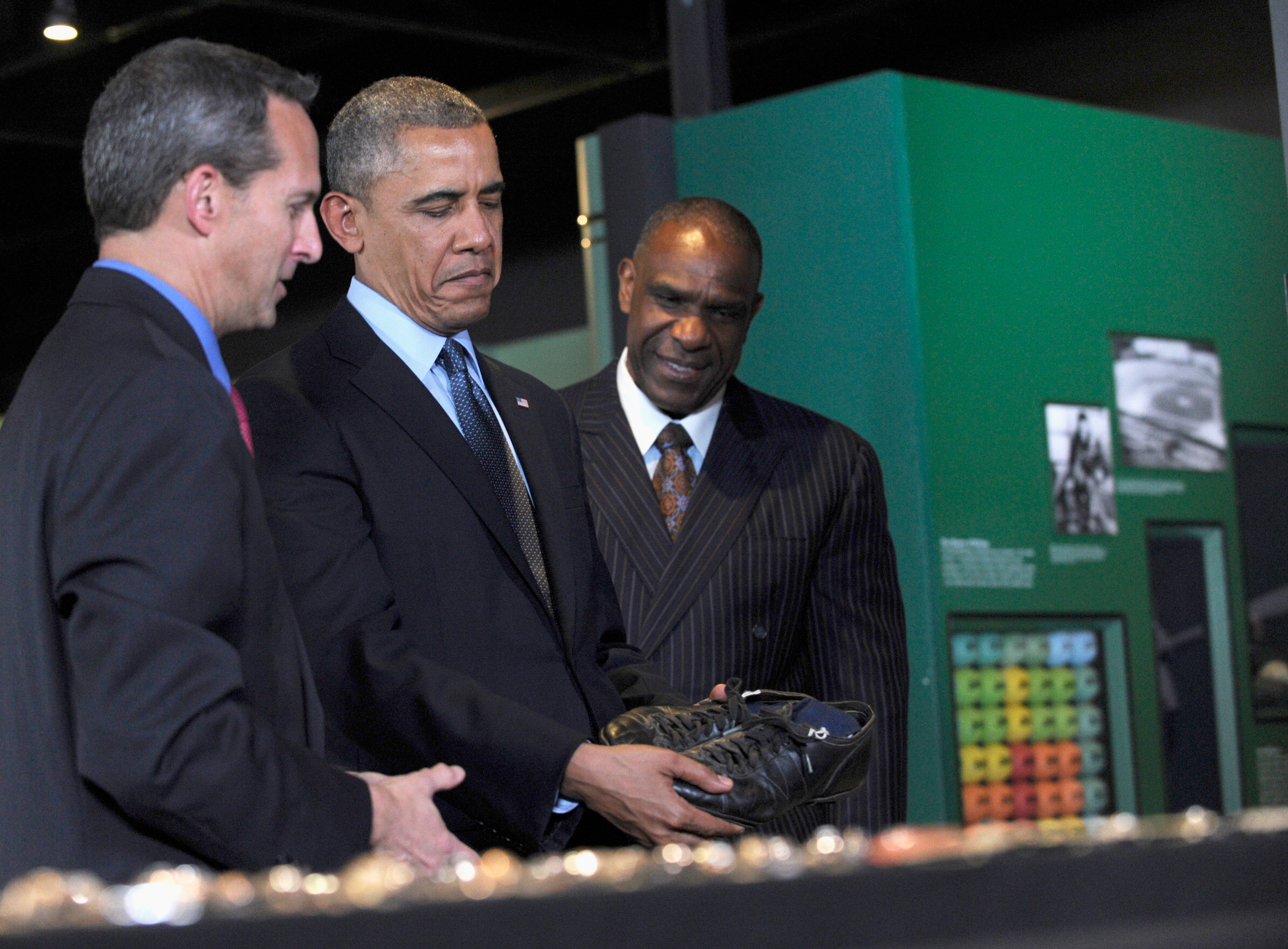 "President Barack Obama, accompanied by Baseball Hall of Fame President Jeff Idelson, left, and baseball hall of fame member Andre Dawson, inducted in 2010, looks at the shoes that ""Shoeless"" Joe Jackson, wore during a tour the Baseball Hall of Fame in Cooperstown, N.Y., Thursday, May 22, 2014. Obama visited the museum to highlight tourism and steps to help spur international visits to the 50 states. Obama said the overall U.S. economy and local businesses will benefit if it isn't a hassle for people from other countries to visit the U.S. and spend money at its hotels, restaurants, tourist destinations and other businesses. (AP Photo/Susan Walsh)"