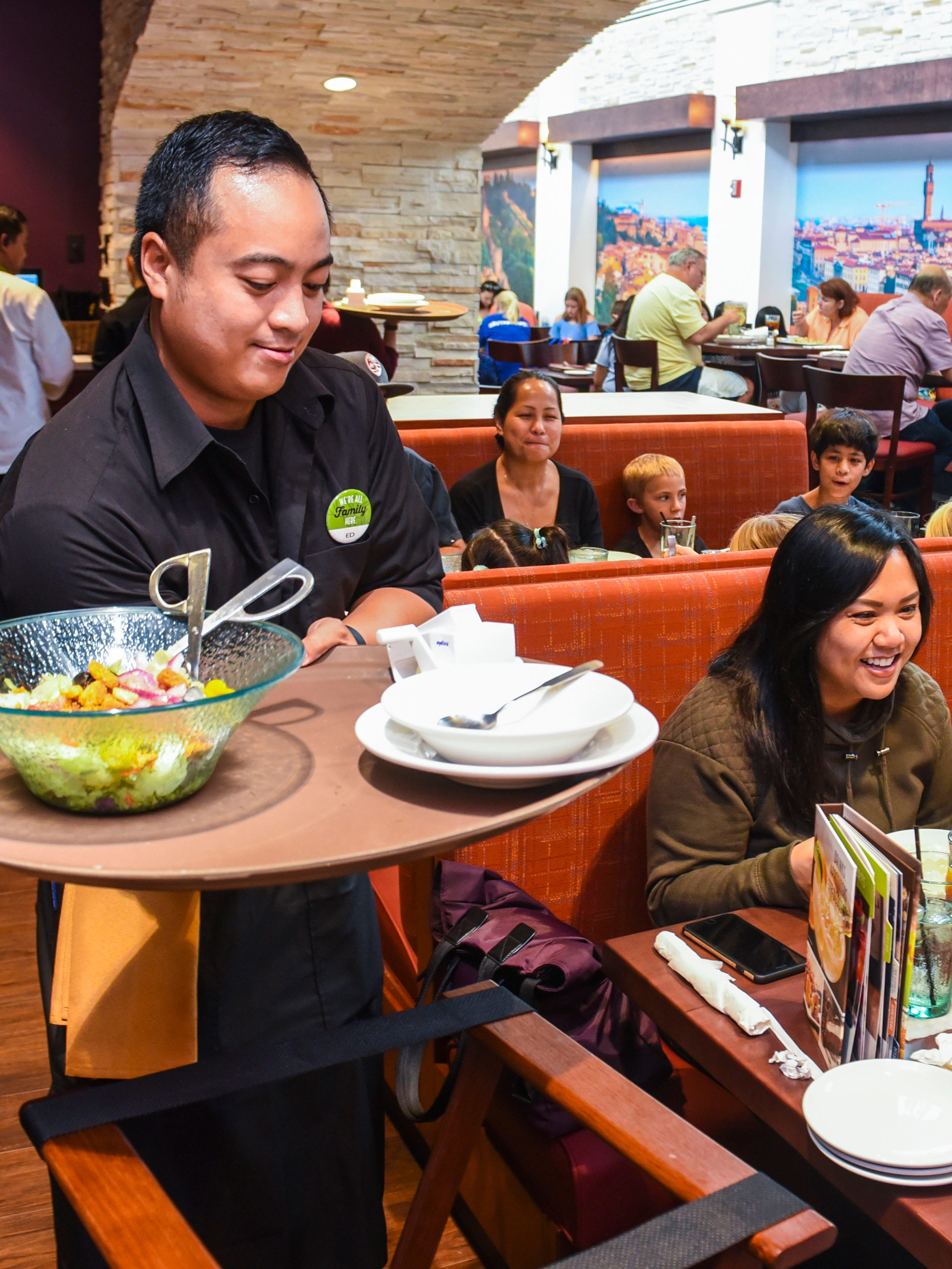 Server Ed Estillore, right, prepares to present diners with part of their order during the first day of business at the Olive Garden restarant in Tumon on Tuesday, Oct. 9, 2018.