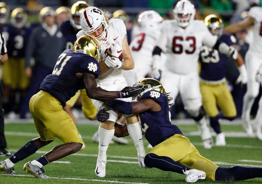 Stanford wide receiver Trenton Irwin is stopped by Notre Dame safety Jalen Elliott (21) and linebacker Asmar Bilal during the first half of an NCAA college football game Saturday, Sept. 29, 2018, in South Bend, Ind. (AP Photo/Carlos Osorio)