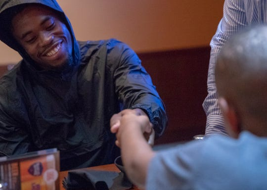 Kenny Moore, a cornerback, shakes a hand during a birthday party for Jack Doyle, tight end for the Indianapolis Colts, at Dave and Busters, Indianapolis, Monday, Oct. 8, 2018.