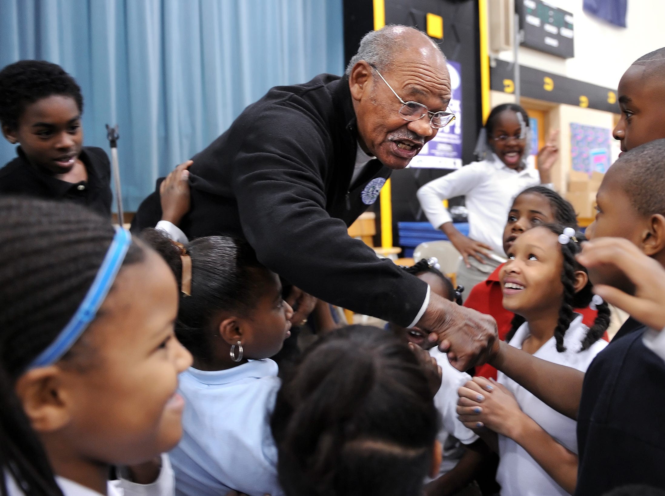 Indiana University football legend George Taliaferro, 91, who was the first African American drafted by the All-American Football Conference back in 1949, shook hands with kids after discussing his personal story of triumph with Robert Lee Frost Elementary School students on Thursday, October 30, 2008.  Taliaferro shared with students how his determination and pursuit of quality education provided the foundation for his success. Here, he talks about a drawing someone made for him back in his glory days. (Matt Detrich / The Star)