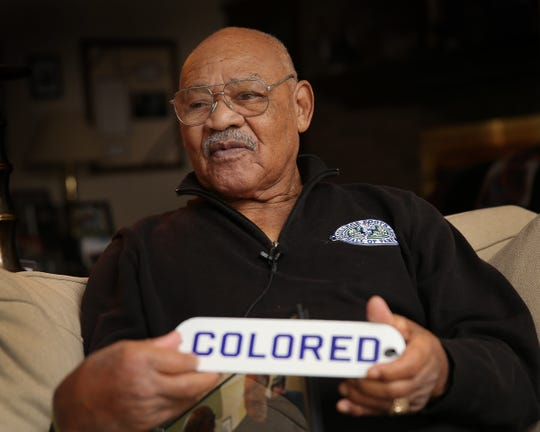 """George Taliaferro, 91, former IU football star, was the first African-American drafted by an NFL team. Here he holds a """"colored"""" sign he took off the wall of the Princess Theatre in Bloomington. African Americans at the time could only go to movies on Friday, Saturday and Sunday and had to sit in the balcony."""