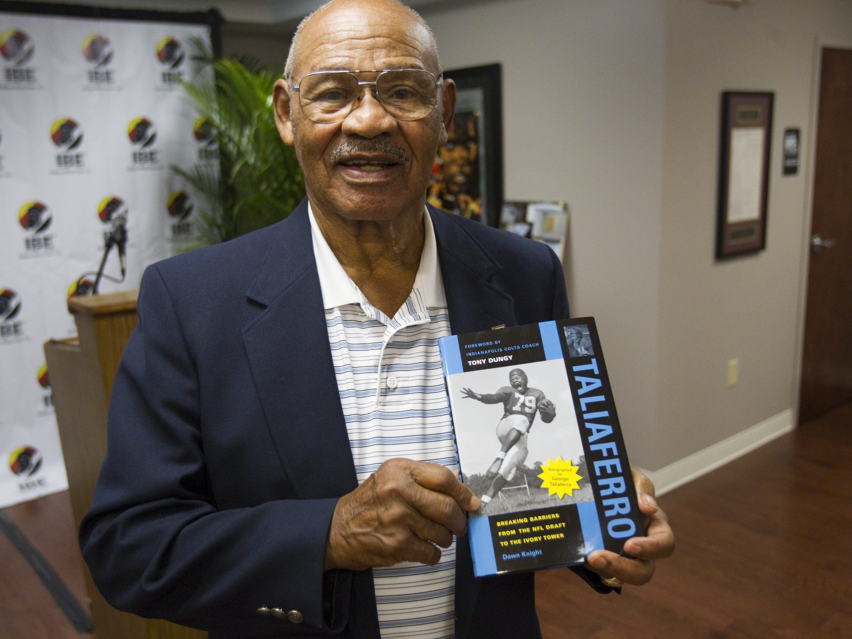 """George Taliaferro, 91, shown when he won the Major Taylor Award in Indianapolis in 2012, was the first African American drafted by the National Football League. The biography he is holding, """"Taliaferro,"""" includes a foreword by former Indianapolis Colts coach Tony Dungy. Robert Scheer/IndyStar"""