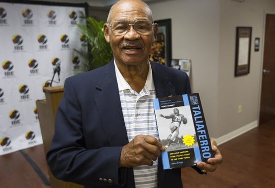 "George Taliaferro, 91, shown when he won the Major Taylor Award in Indianapolis in 2012, was the first African American drafted by the National Football League. The biography he is holding, ""Taliaferro,"" includes a foreword by former Indianapolis Colts coach Tony Dungy. Robert Scheer/IndyStar"
