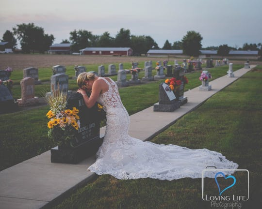 Jessica Padgett kneels at the headstone of her fiancé, Kendall Murphy, who was killed in Daviess County last year while on duty as a volunteer firefighter.