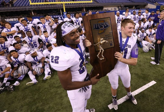 Ben Davis Giants Asmar Bilal and Kyle Castner, right, celebrate their win. Giants defeated Carmel Greyhounds 42-24 in the IHSAA Class 6A State Football Championship game, Nov. 28, 2014, at Lucas Oil Stadium.