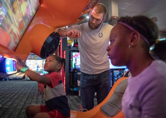 Jazariah Ware, 12 (right), and an unidentified child play a game with Jack Doyle, tight end for the Indianapolis Colts, at Dave and Busters, Indianapolis, Monday, Oct. 8, 2018. About 15 kids from Dayspring Center in Indianapolis joined Doyle, his wife, and several other Colts players for the event that honored some of the kids' birthdays, and gave them a good meal and an afternoon of games at the venue.