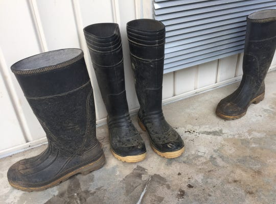 Migrant farmworkers' boots sit outside rooms at a roadside motel in Carlyle, Indiana.