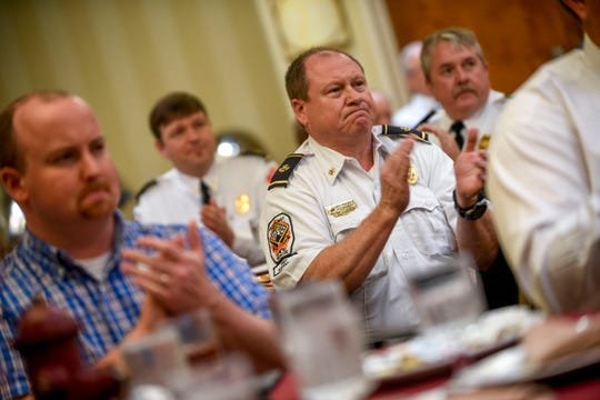 Russell Downen, battalion chief of the Jackson City Fire Department, claps for Paul Cook after Cook was presented the firefighter of the year award at a meeting held by the Exchange Club of Jackson at DoubleTree Hilton Hotel in Jackson, Tenn., on Tuesday, Oct. 9, 2018.