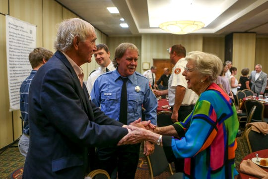 Ann Cook, right, mother of Paul Cook, shakes hands with and is greeted by mayor Jerry Gist at a meeting held by the Exchange Club of Jackson at DoubleTree Hilton Hotel in Jackson, Tenn., on Tuesday, Oct. 9, 2018.
