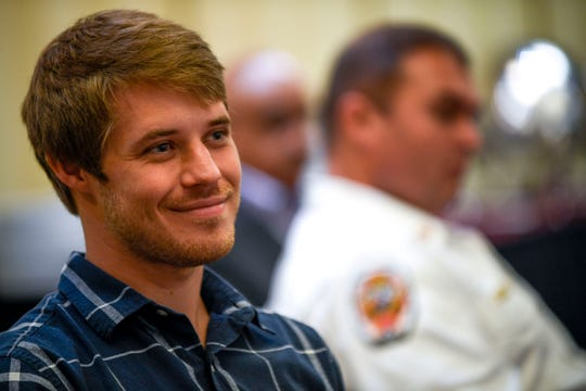 Caleb Cook, the son of Paul Cook, smiles while listening to his father thank his fellow firefighters for their service after being presented the firefighter of the year award at a meeting held by the Exchange Club of Jackson at DoubleTree Hilton Hotel in Jackson, Tenn., on Tuesday, Oct. 9, 2018.