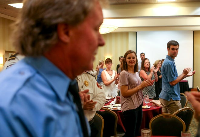 Exchange Club members stand and applaud Paul Cook before he is presented a firefighter of the year award at a meeting held by the Exchange Club of Jackson at DoubleTree Hilton Hotel in Jackson, Tenn., on Tuesday, Oct. 9, 2018.