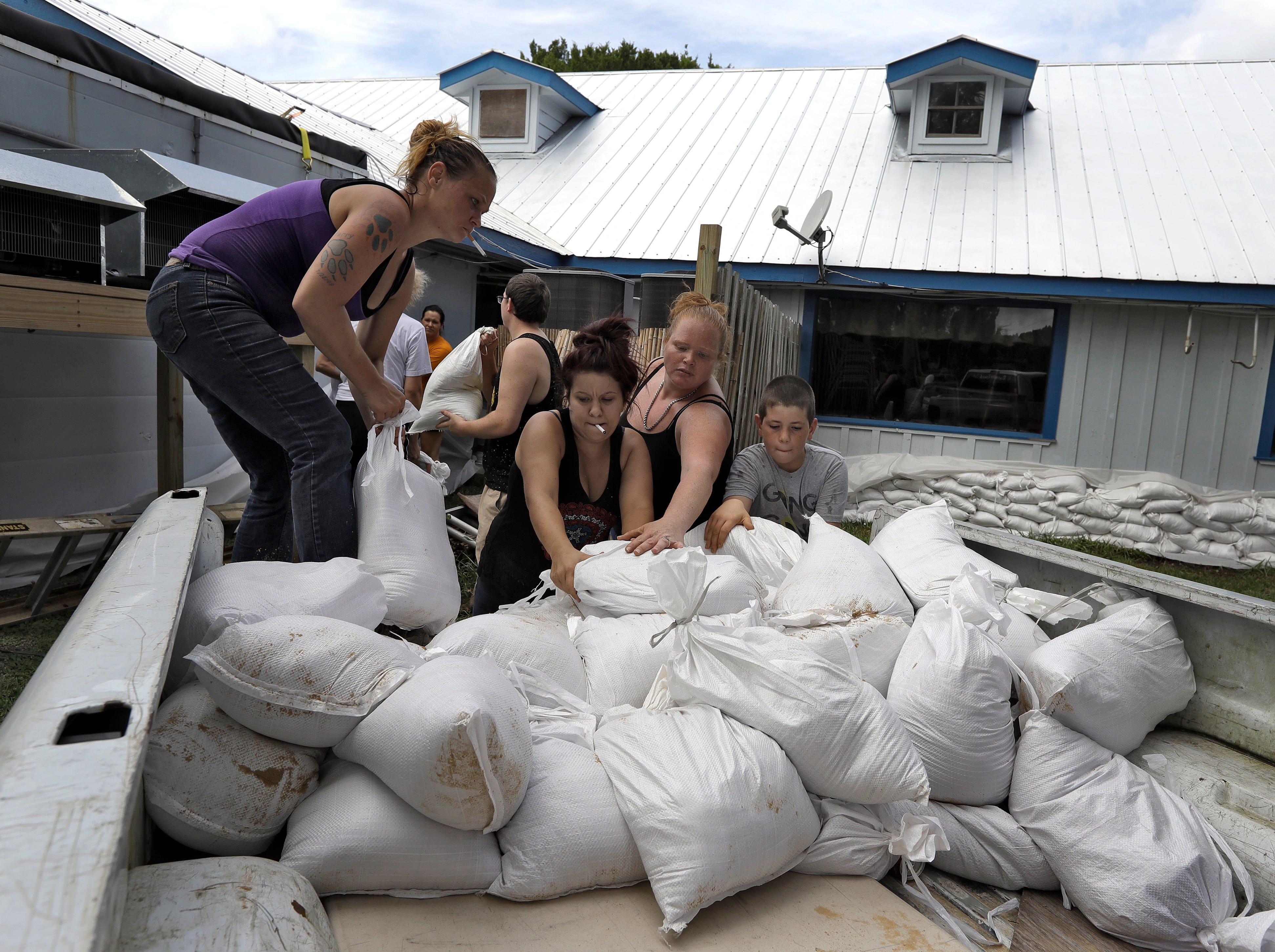 Krystal Day, of Homosassa, Fla., left, leads a sandbag assembly line at the Old Port Cove restaurant Tuesday, Oct. 9, 2018, in Ozello, Fla. Employees were hoping to protect the restaurant from floodwaters as Hurricane Michael continues to churn in the Gulf of Mexico heading for the Florida panhandle.