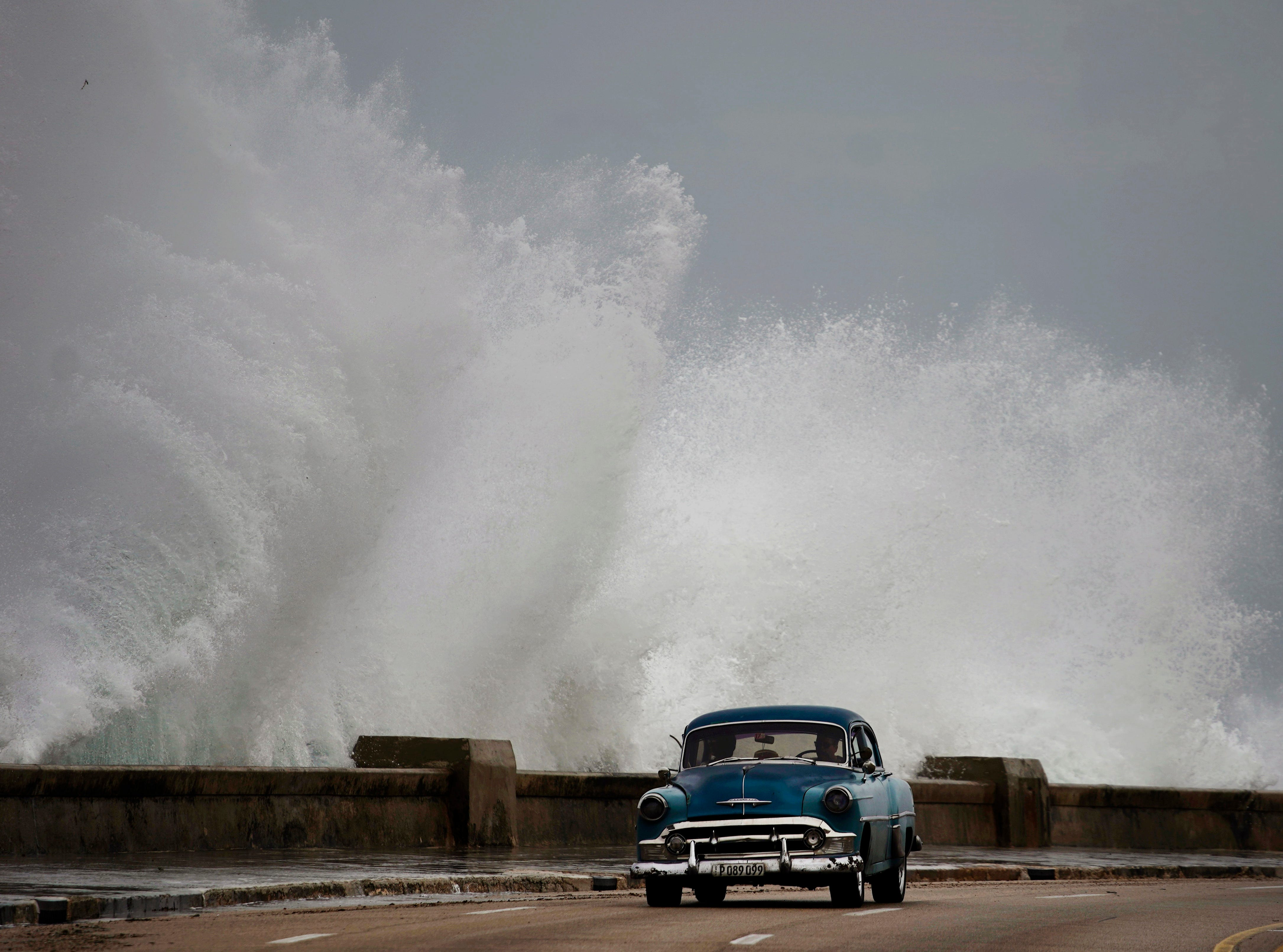 Waves crash against the Malecon, triggered by the outer bands of Hurricane Michael, as man drives past in a classic American car in Havana, Cuba, Tuesday, Oct. 9, 2018. A fast and furious Hurricane Michael is churning toward the Florida Panhandle with 110 mph winds and a potential storm surge of 12 feet, giving tens of thousands of people precious little time to get out.