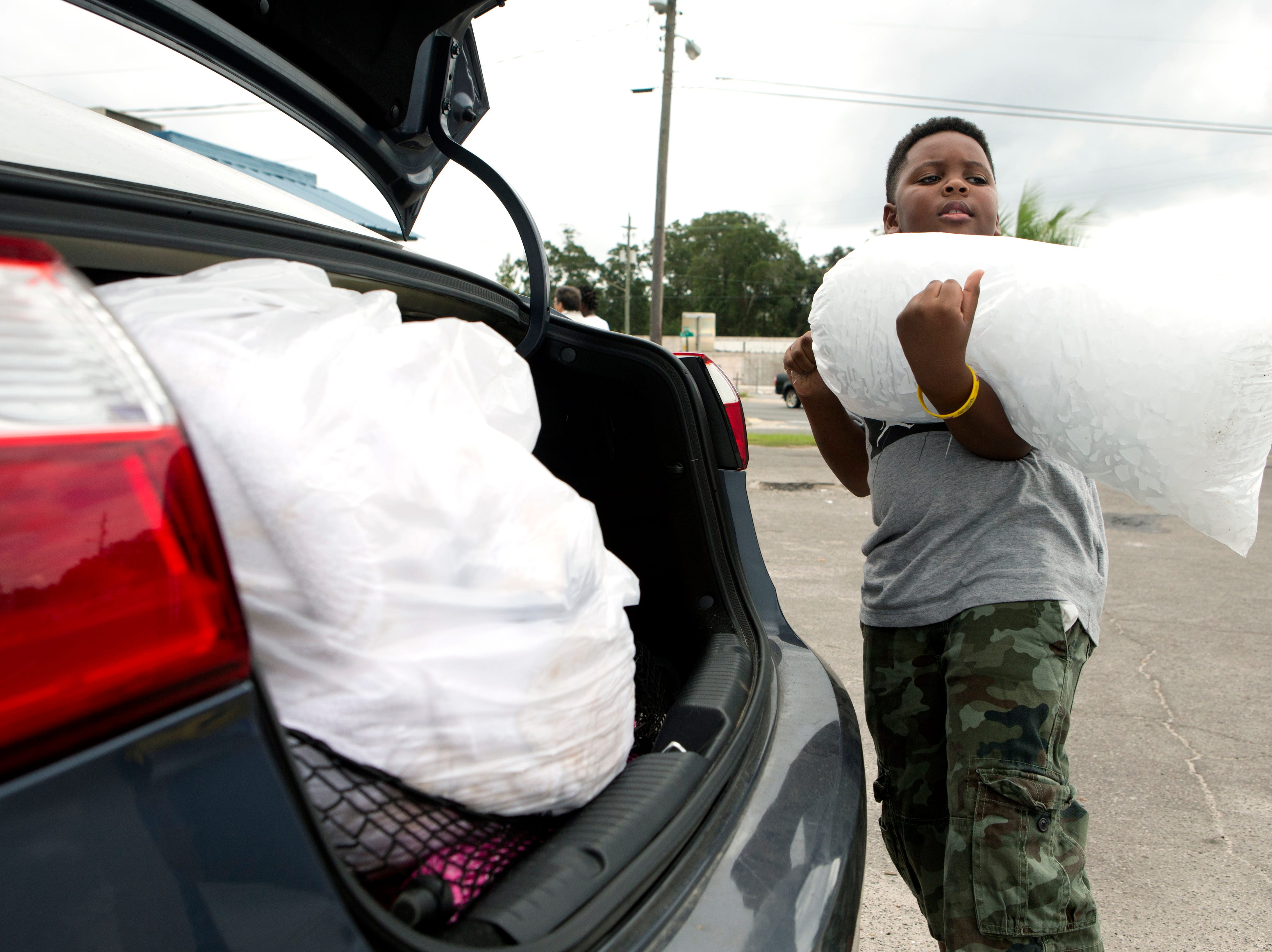 Xavier McKenzie puts a twenty pound bag of ice into his family's car in Panama City, Fla., as Hurricane Michael approaches on Tuesday, Oct.9, 2018. He and his family do not live in a storm surge area, and instead prepared for losing power for days.
