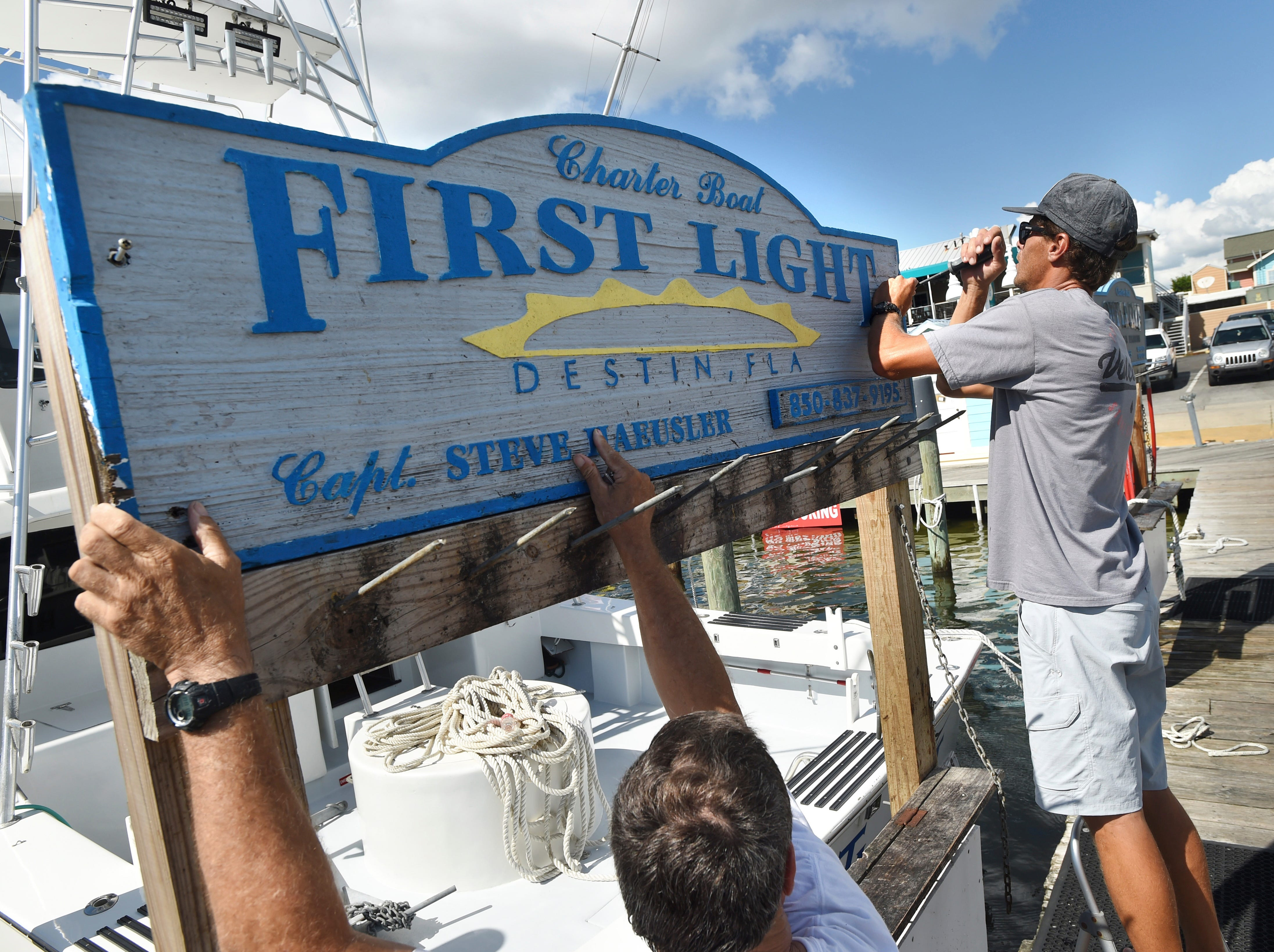 """Capt. Steve Haeusler, left, and Wyatt Ferreira take down the sign for Haeusler's charter fishing boat """"First Light"""" on Monday, Oct. 8, 2018. Boat captains in this fishing community were relocating their vessels to safer locations in advance of Hurricane Michael."""