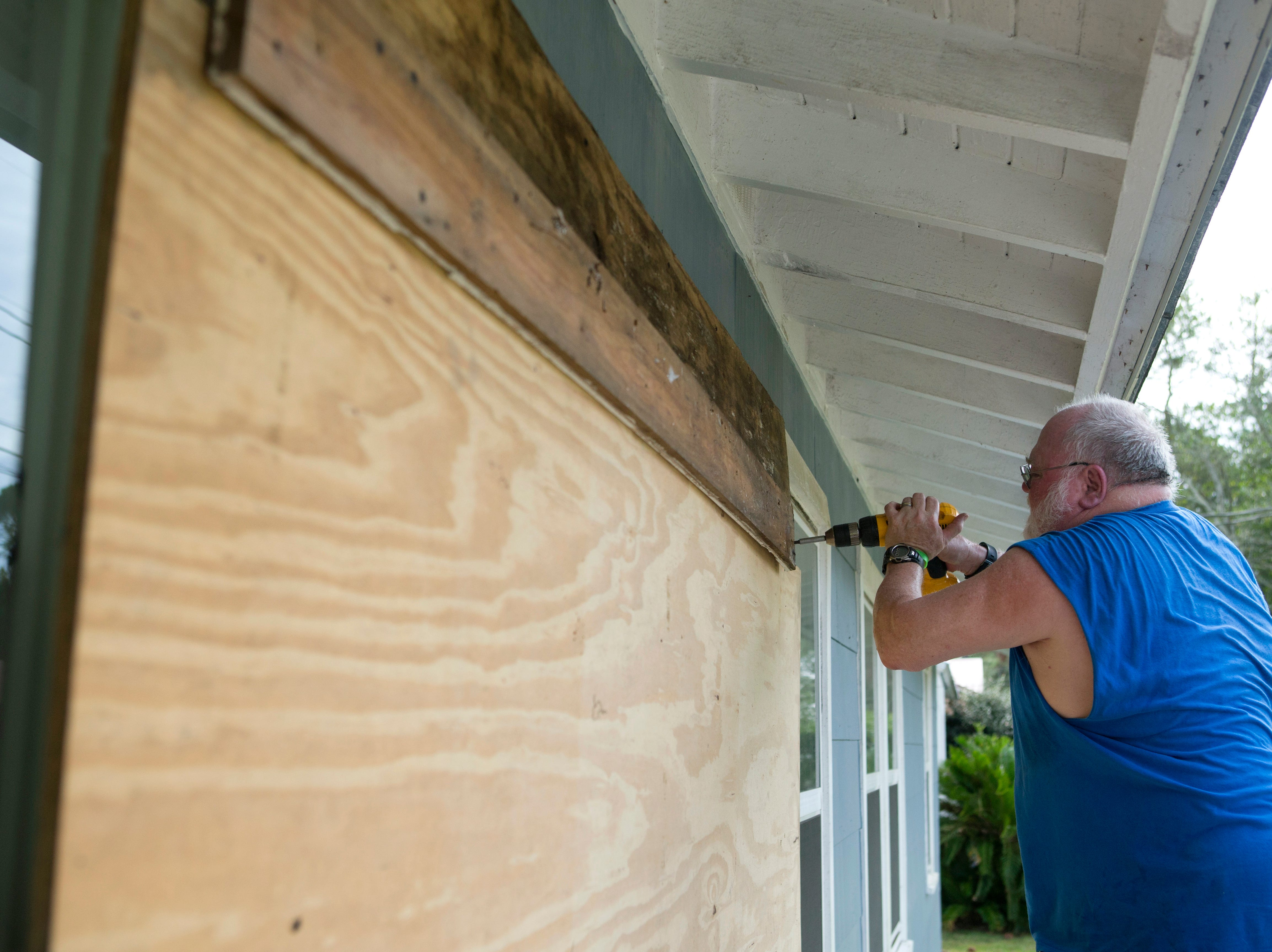 David Hayes boards up a window at this home in Panama City, Fla., as Hurricane Michael approaches on Tuesday, Oct. 9, 2018.