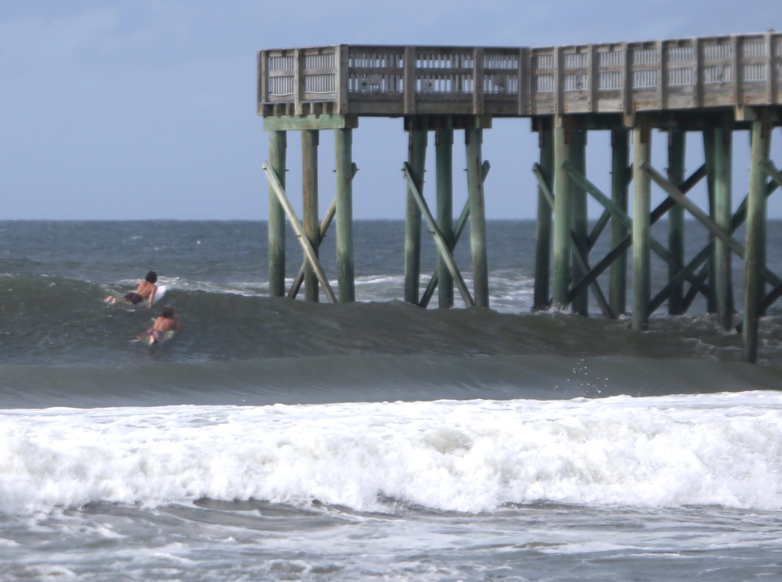 Surfers paddle past the St.Andrews State Park Pier Tuesday, Oct.9, 2018,  at Panama City Beach, Fla.