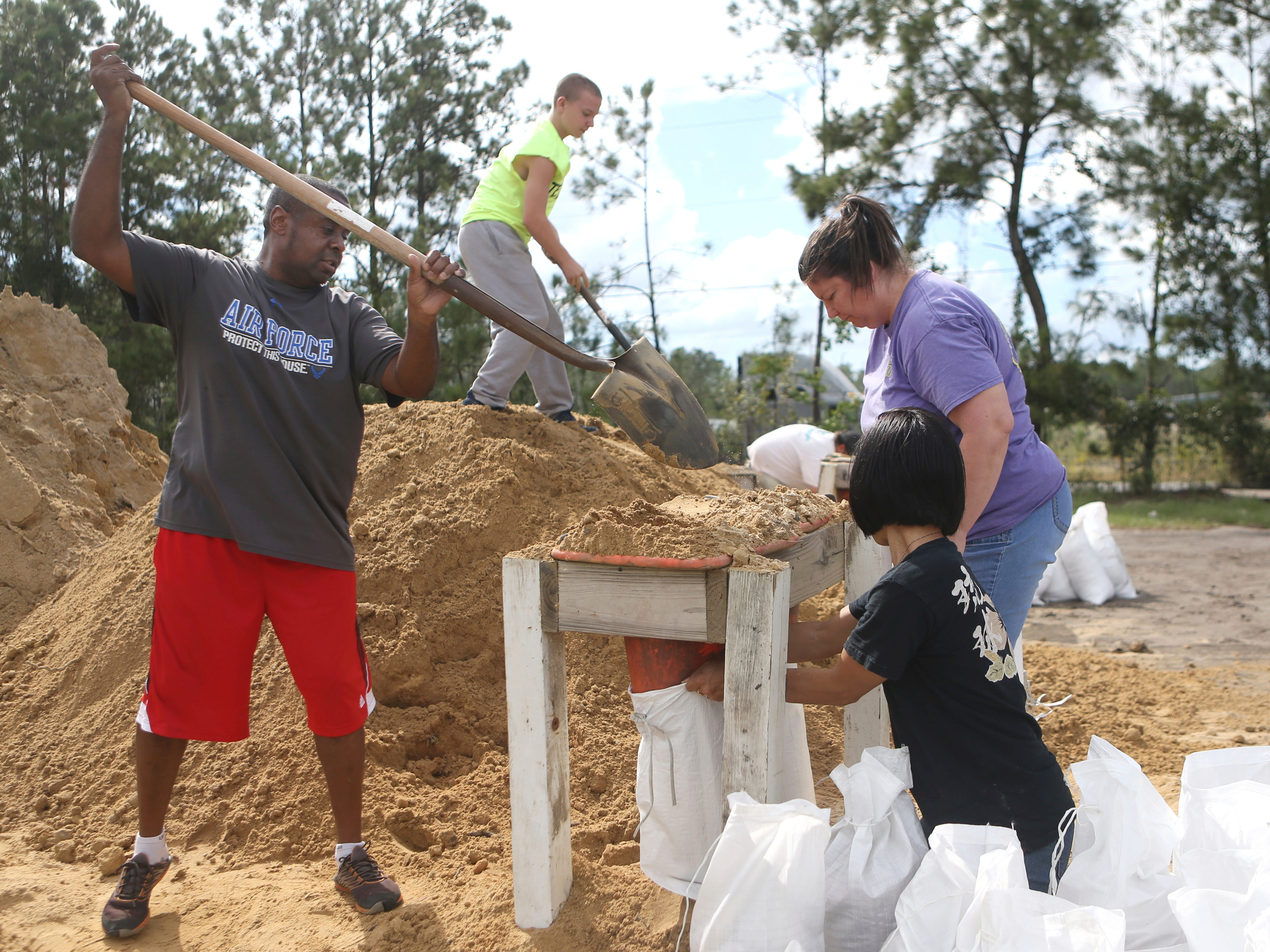 From left, Haskel Johnson, Daniel Tippett, Jennifer Tippett and Nobuko Johnson fill sand bags at the Lynn Haven Sports Complex in Lynn Haven, Fla., Monday, Oct. 8, 2018, to prepare for Hurricane Michael.