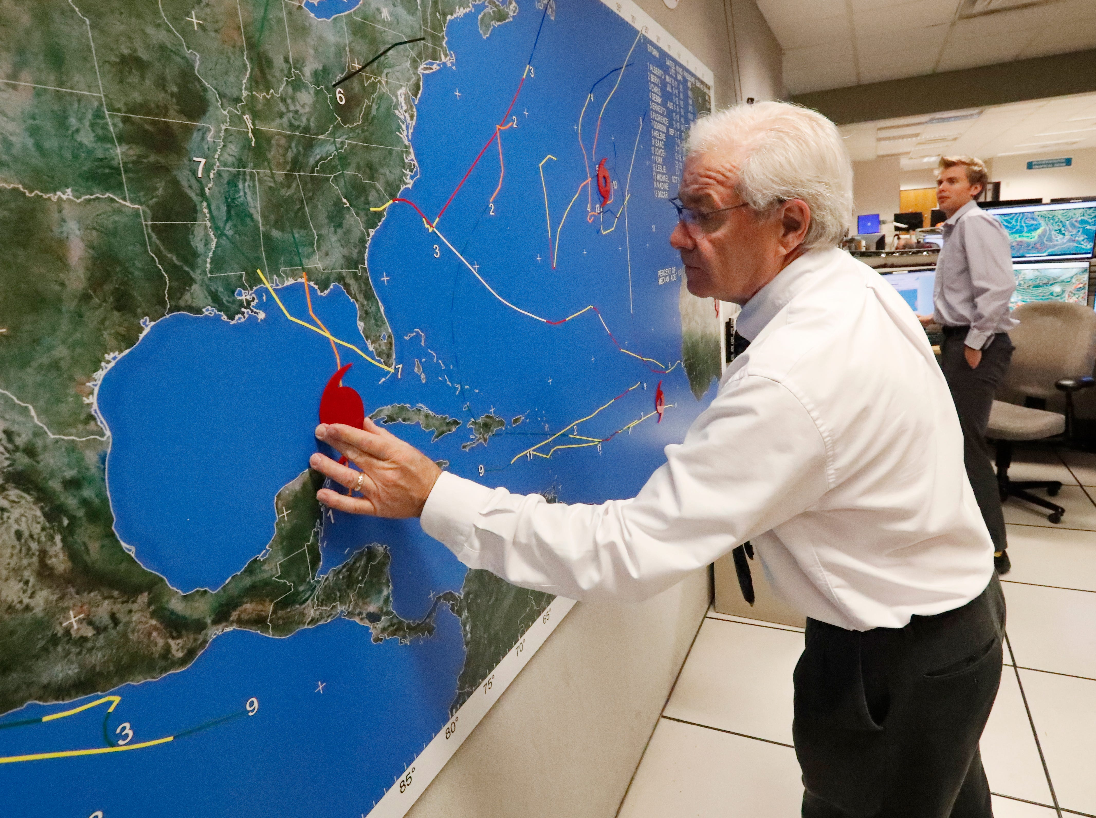 National Oceanic and Atmospheric Administration public affairs officer Dennis Feltgen updates the progress of Hurricane Michael on a large map, Tuesday, Oct. 9, 2018, at the Hurricane Center in Miami.