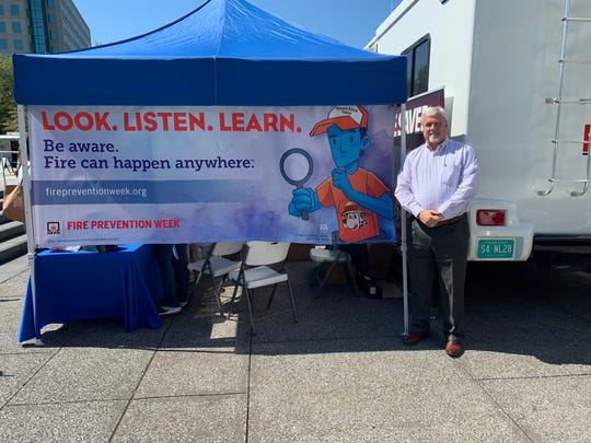 Assistant Commissioner of Fire Prevention Gary Farley poses with the Fire Prevention Week banner at an event for it.