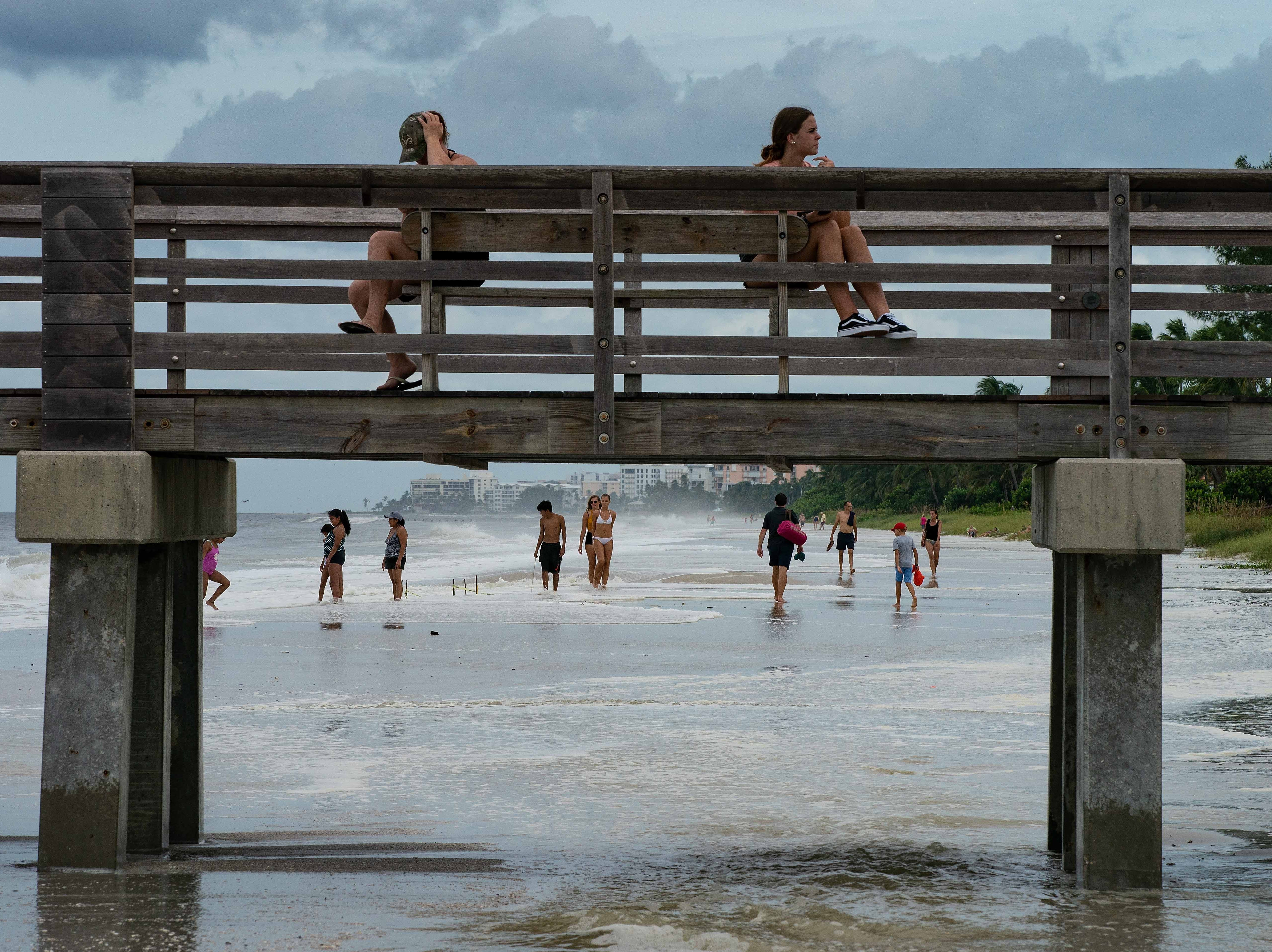 Oct. 9, 2018; Naples, FL, USA; Beach goers walk on the beach near the Naples Pier as Hurricane Michael wind pushes the water close to the dune.
