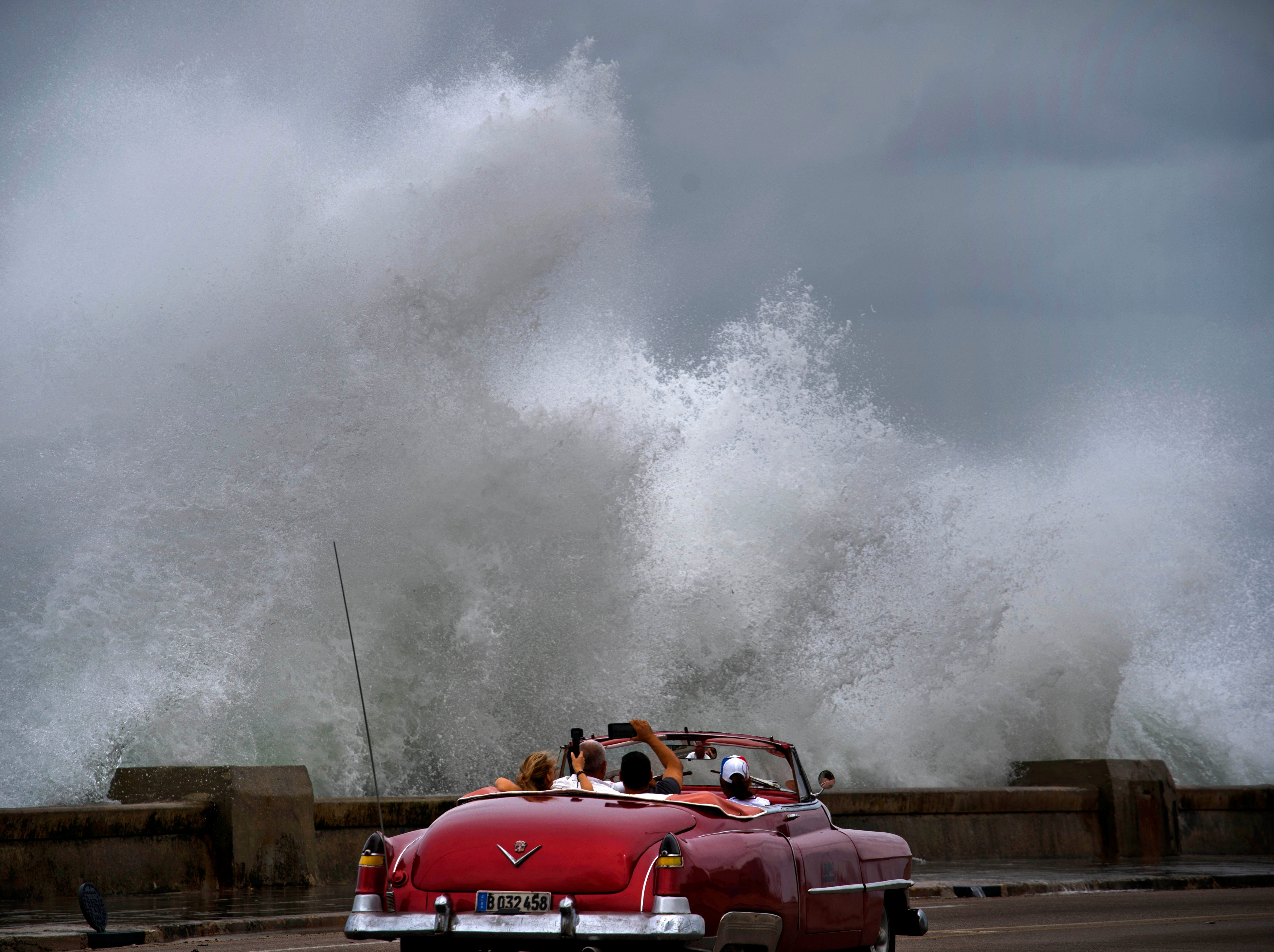 Waves crash against the Malecon, triggered by the outer bands of Hurricane Michael, as tourists drive past in a classic American car in Havana, Cuba, Tuesday, Oct. 9, 2018. A fast and furious Hurricane Michael is churning toward the Florida Panhandle with 110 mph winds and a potential storm surge of 12 feet, giving tens of thousands of people precious little time to get out.