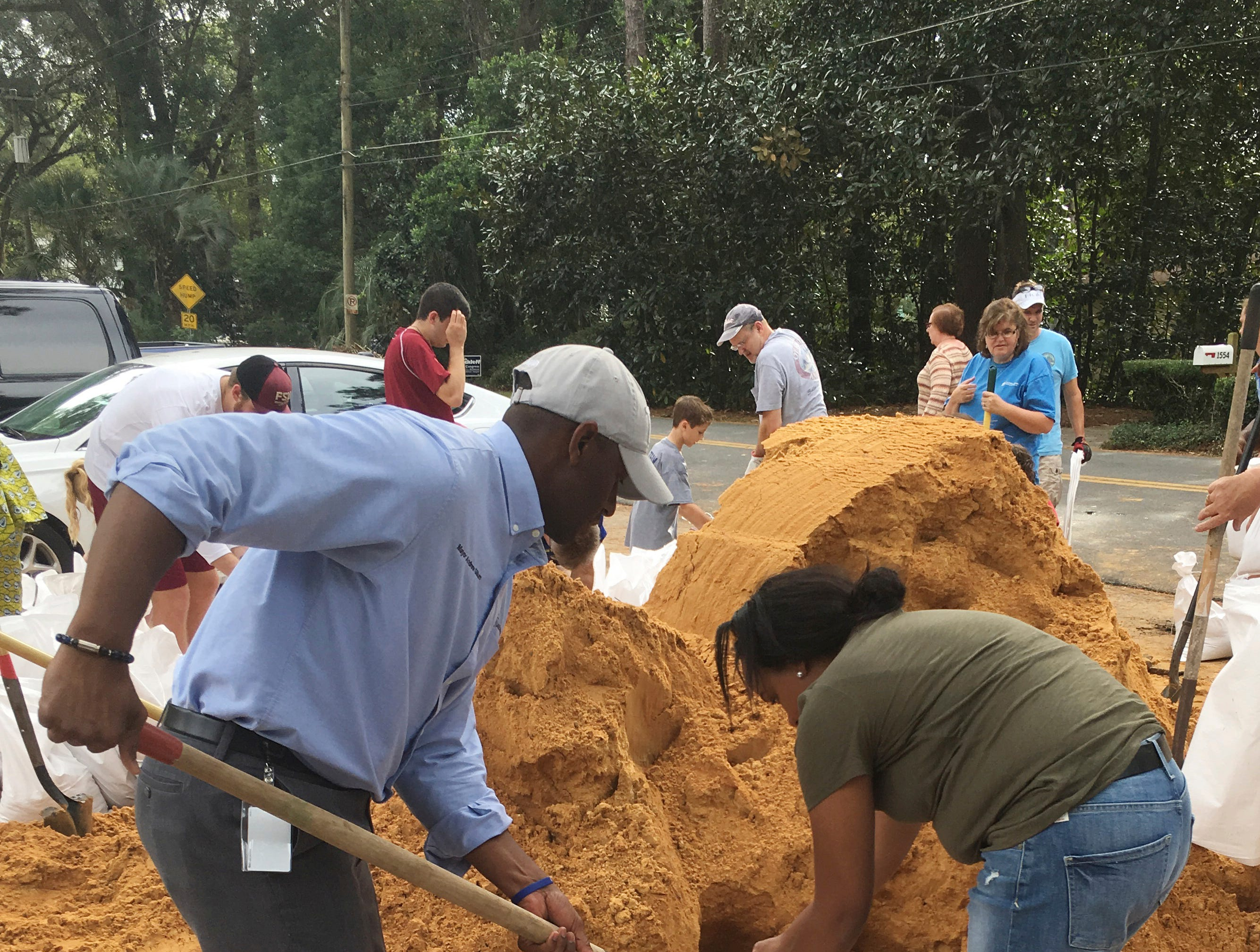 Tallahassee Mayor and Democratic gubernatorial candidate, Andrew Gillum, left, helps Eboni Sipling fill up sandbags in Tallahassee, Fla., Monday, Oct. 8, 2018. Residents in Florida's Panhandle and Big Bend are getting ready for Hurricane Michael, which is expected to make landfall by midweek.