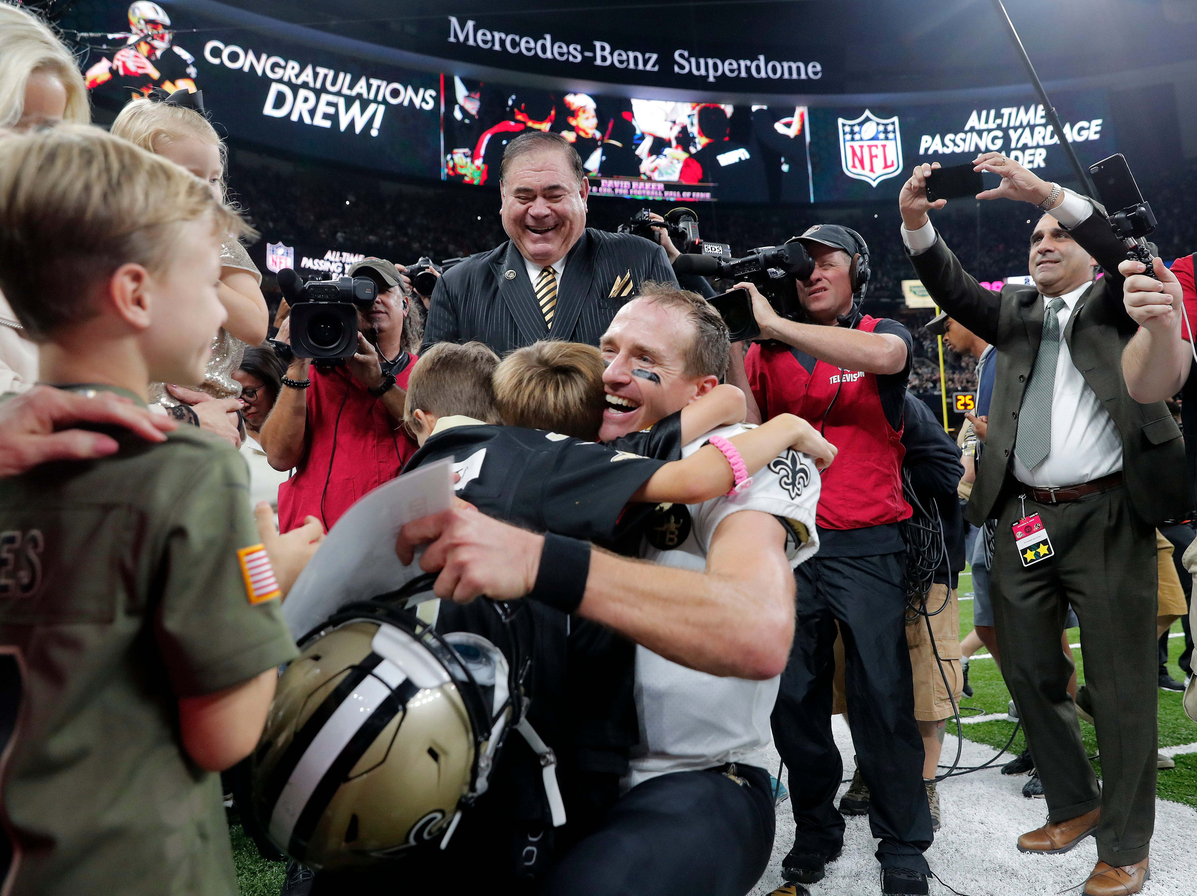 New Orleans Saints quarterback Drew Brees (9) hugs his family after breaking the NFL all-time passing record in the first half of an NFL football game against the Washington Redskins in New Orleans, Monday, Oct. 8, 2018. (AP Photo/Gerald Herbert)