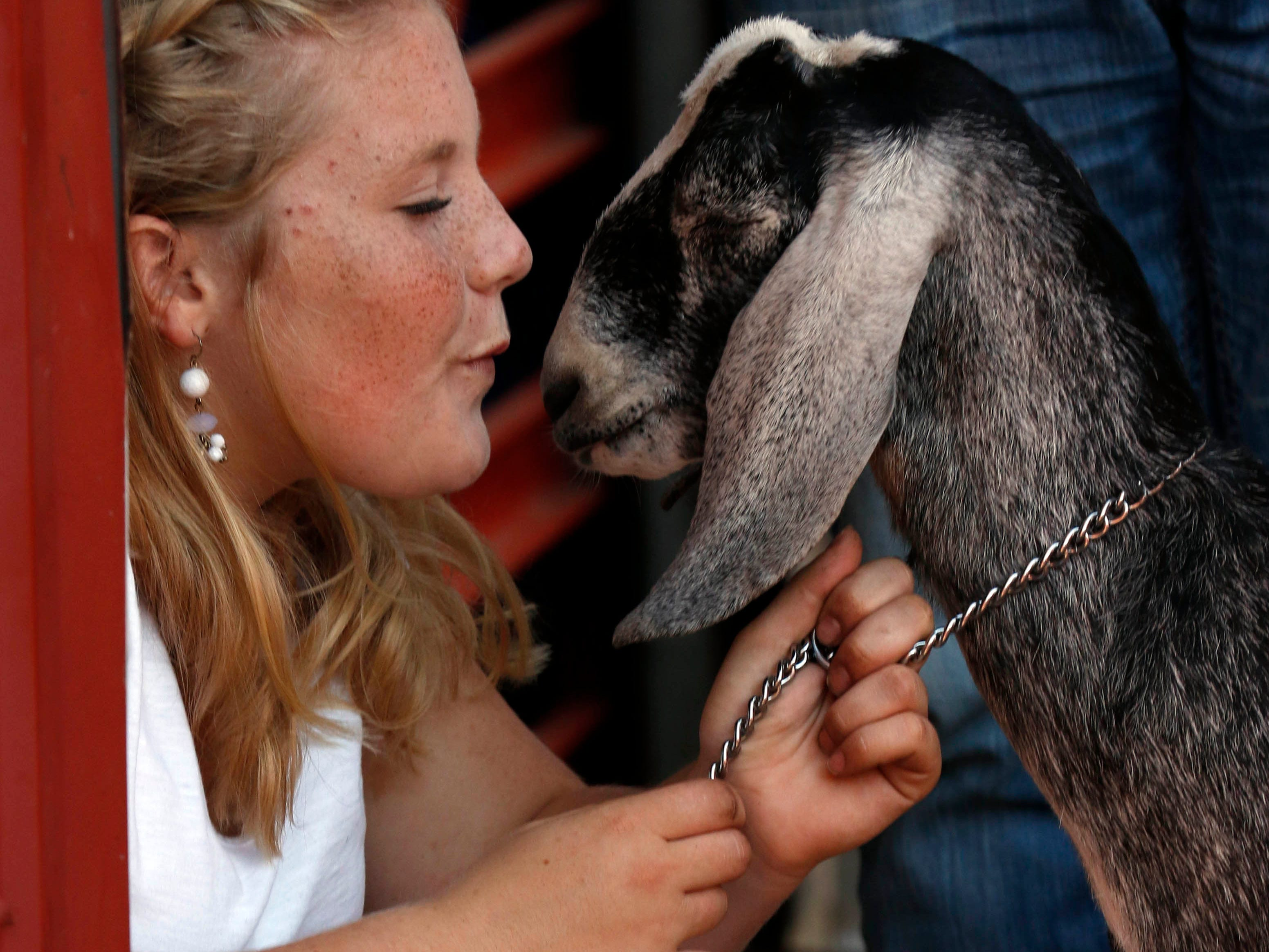 Tatum Campbell kneels next to her goat as they wait for their class of showmanship to begin Tuesday, Oct. 9, 2018, at the Fairfield County Fair in Lancaster.