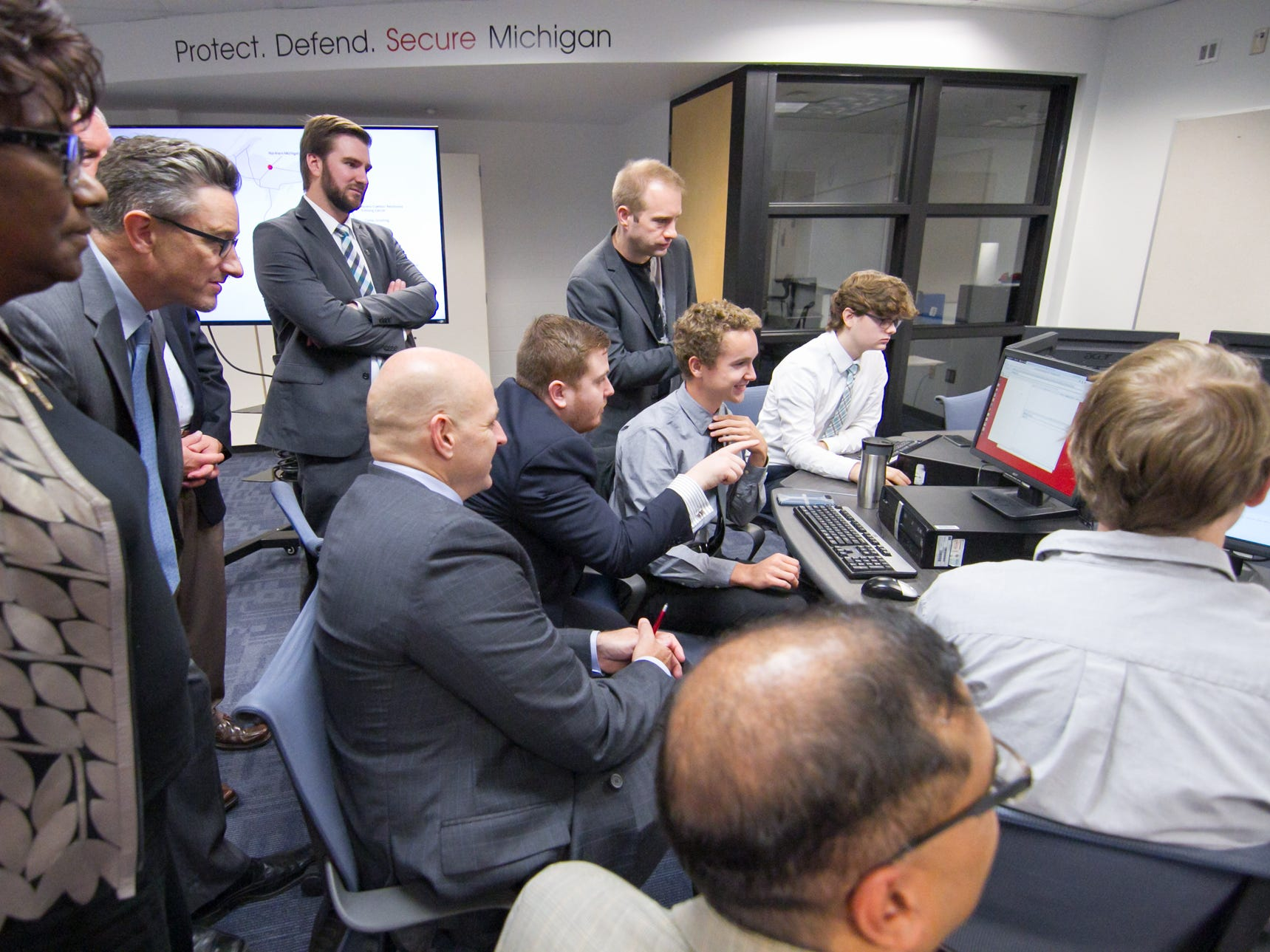 """IBM executives touring the Pinckney Cyber Training Institute Tuesday, Oct. 9, 2018 appear to get into a game of """"capture the flag"""" students are playing."""