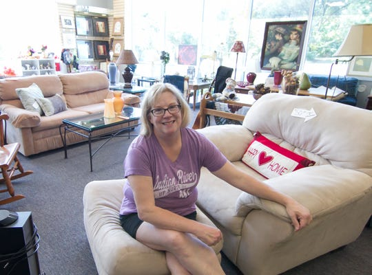 Jennifer Bigelow, Second Chance Support Network executive director, sits on a piece of donated furniture Tuesday, Oct. 9, 2018 inside the recently opened Second Chance Resale Shop in Brighton Township.