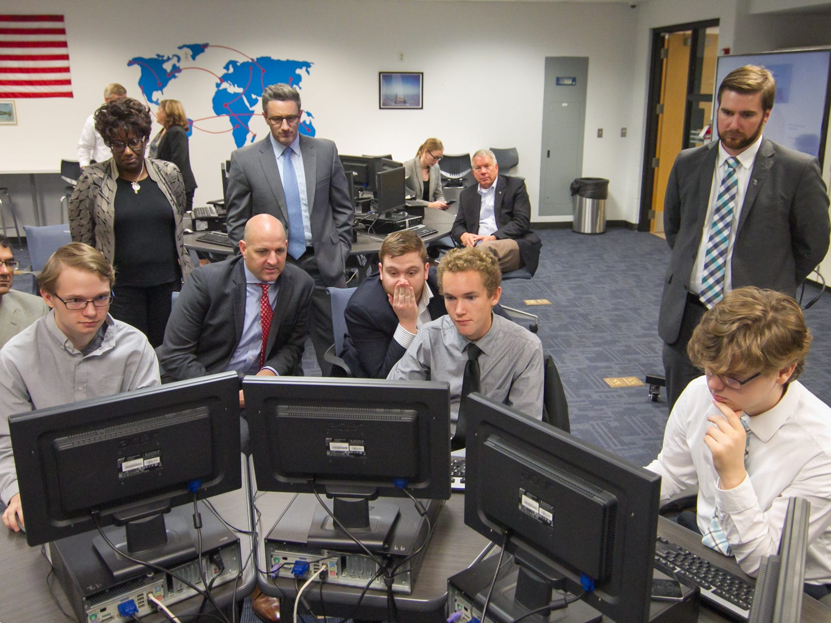 """From left, Pinckney Cyber Training Institute students Noah Warner, Luke Flickema and Aidan Ozias, all seniors, play """"capture the flag,"""" a cyber security game, Tuesday, Oct. 9, 2018 as executives from IBM look on."""