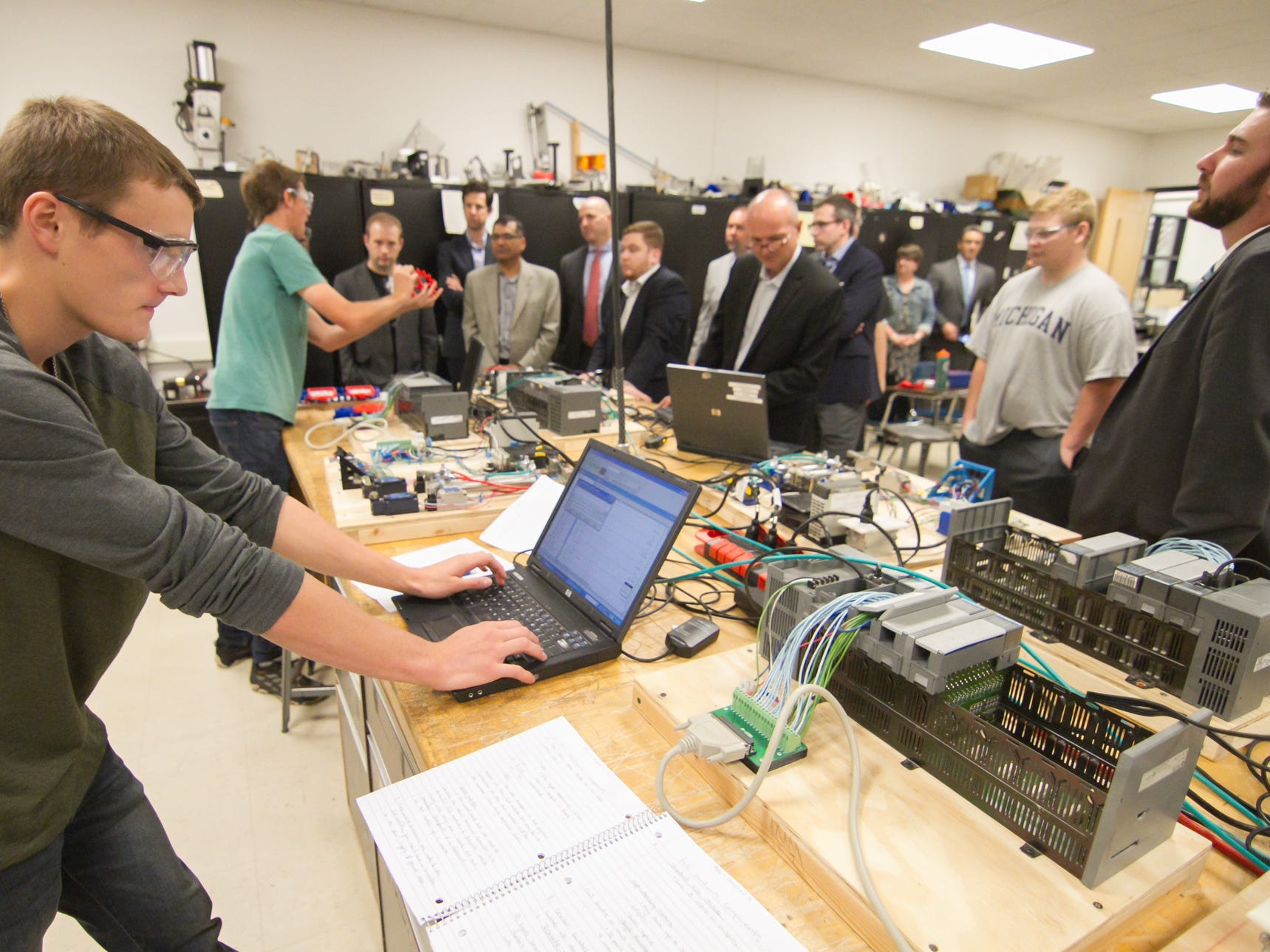 Pinckney Cyber Training Institute junior Nick Cortez (foreground) works on a program to run a robotic process Tuesday, Oct. 9, 2018, with senior Blake Mahnken in the background as students show what they're learningin the program to IBM executives touring the facility at Pinckney Community High School.