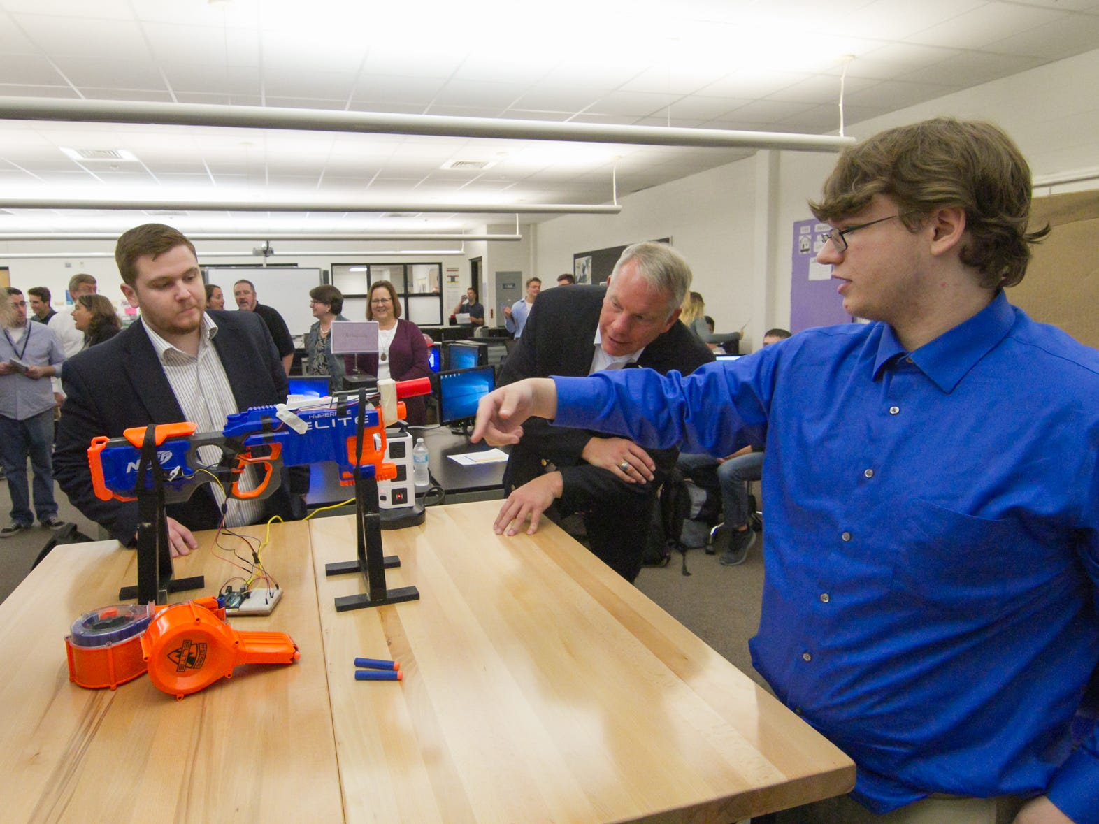 Pinckney Cyber Training Institute senior Jacob Velasco, left, explains the engineering behind the autonomous Nerf Blaster he designed which shoots a burst of Nerf bullets when someone passes in front of it. The demonstration was part of a tour for IBM executives of Pinckney's Cyber Training Institute Tuesday, Oct. 9, 2018.