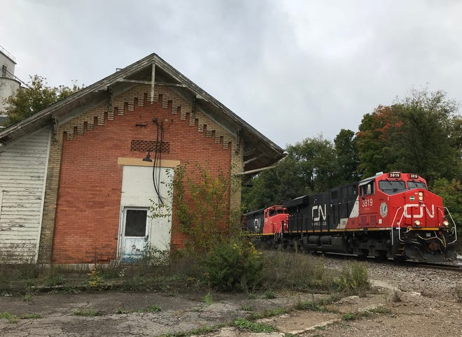 A Canadian National Railroad train thunders past the century-old Grand Trunk Station off North Cochran Avenue in Charlotte. A local effort is underway to save the building.
