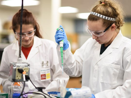 Bioscience careers students Kelsey Andrews, right, and Faith Worthington, both juniors, test their accuracy in making solutions, Thursday, Oct. 4, 2018, at the Wilson Talent Center  in Mason.