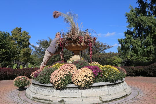 "Ellen Azotea, perennials gardener at Kingwood Center, adds to a fall cuttings arrangement Tuesday in the garden's terrace fountain. ""It took us a couple of days to put it together,"" Azotea said. The gardens will remain open 9 a.m. to 7 p.m. daily through the end of October."