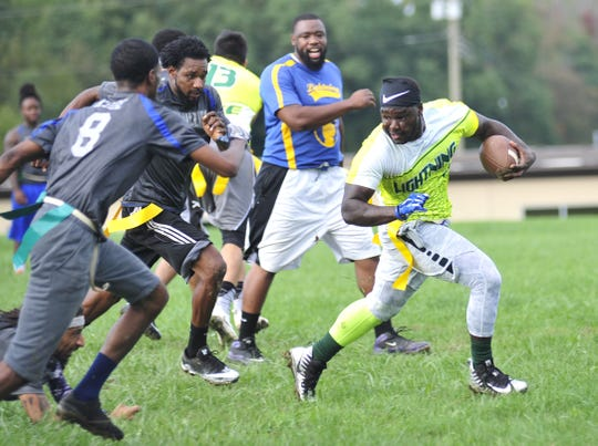 Travon Harris of Team Lightning runs from pursuit during MAD Bowl IV, the championship game of the MAD Adult Flag Football League, last Saturday at John Sherman Elementary School. Team Lightning won its third straight title with a 20-14 victory.