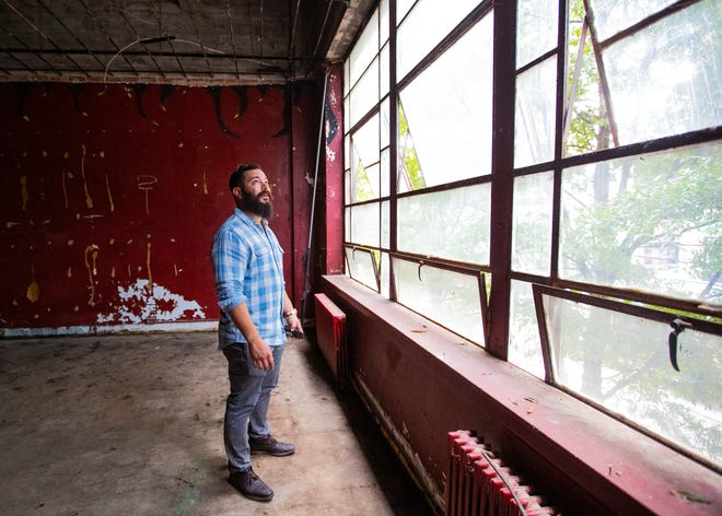 Gabriel Velasquez looks out the windows on the second floor of the up and coming nixed use space on 64 South Main Street on Tuesday.