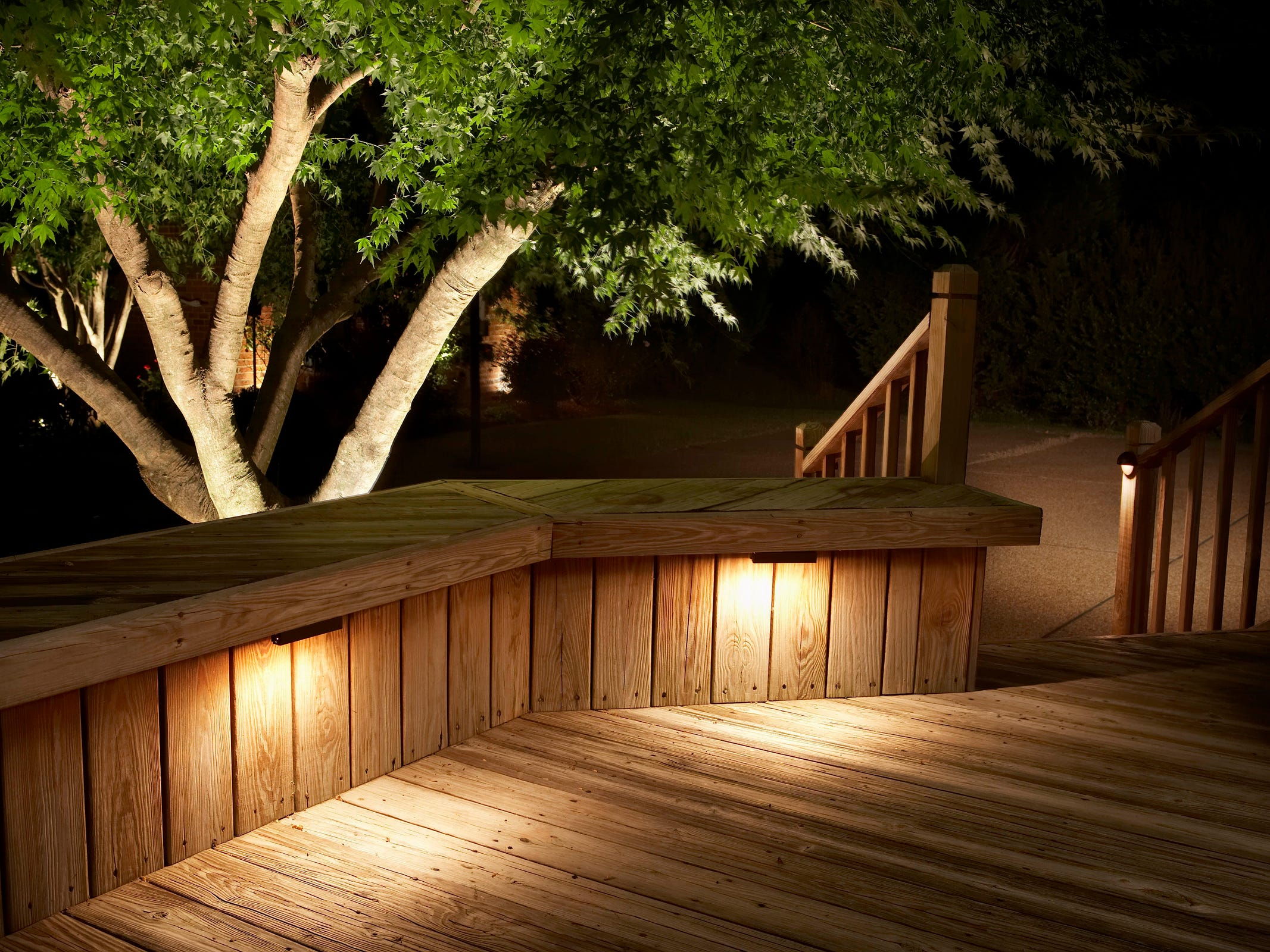 Deck lighting that shines down, and a spotlight that accents a tree add interest to a home and garden.