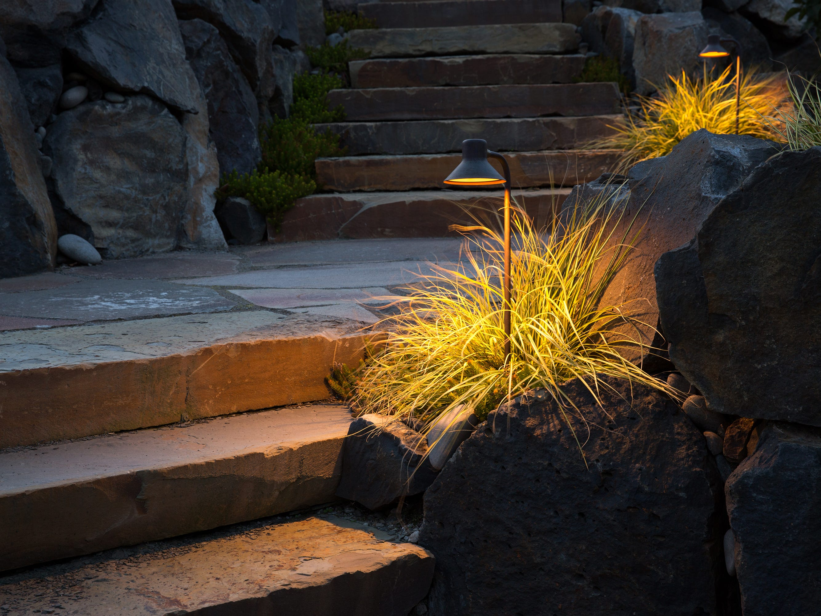 A two-level stone stairway is accented with path lights that keep the area safe, but also highlight ornamental grasses nearby.