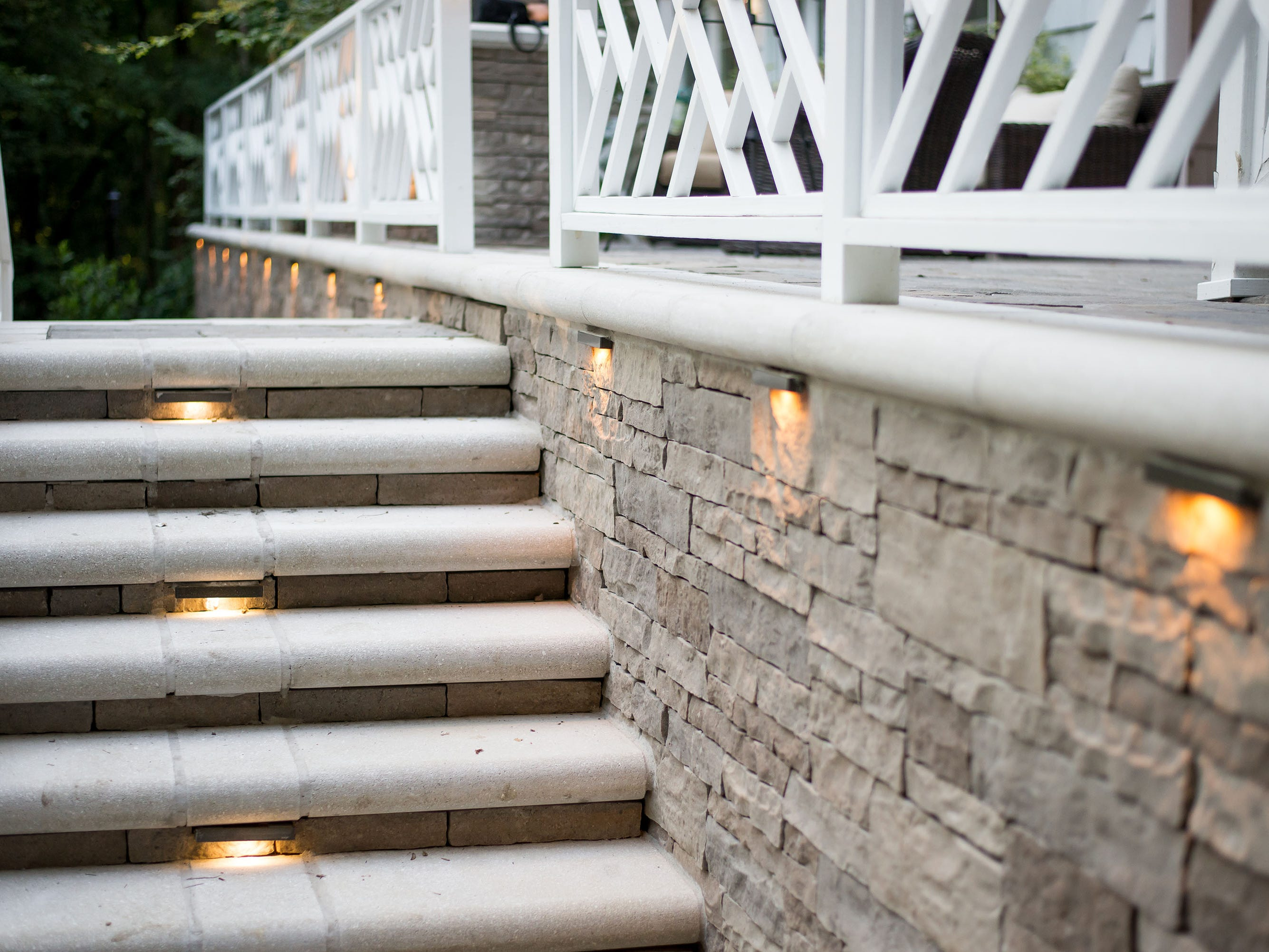 Lights within the steps and along the wall illuminate this outdoor space.