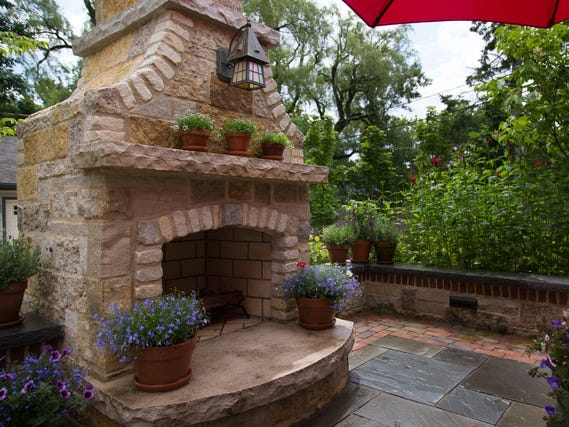 This stone outdoor fireplace is highlighted at night by a large fixture that shines light down onto the stone.