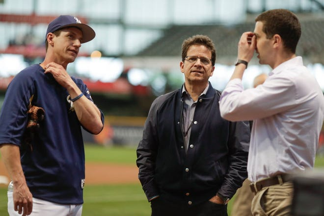 Milwaukee Brewers owner Mark Attanasio (center) talks to manager Craig Counsell (left) and general manager David Stearns before a baseball game against the St. Louis Cardinals on June 21 in Milwaukee.