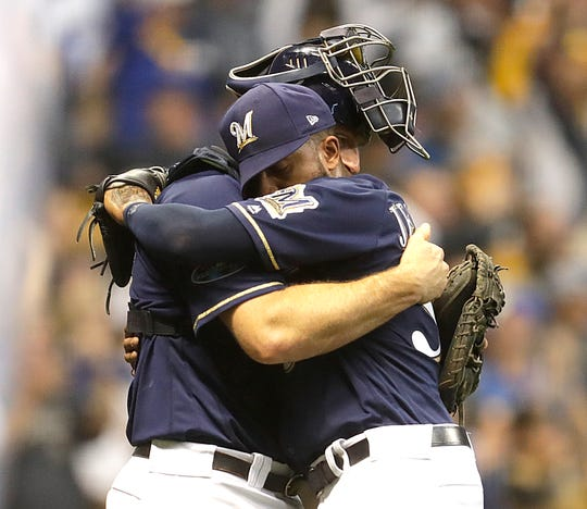 Jeremy Jeffress (right) hugs catcher Erik Kratz after striking out the last Rockies hitter in Game 2 of the NLDS.