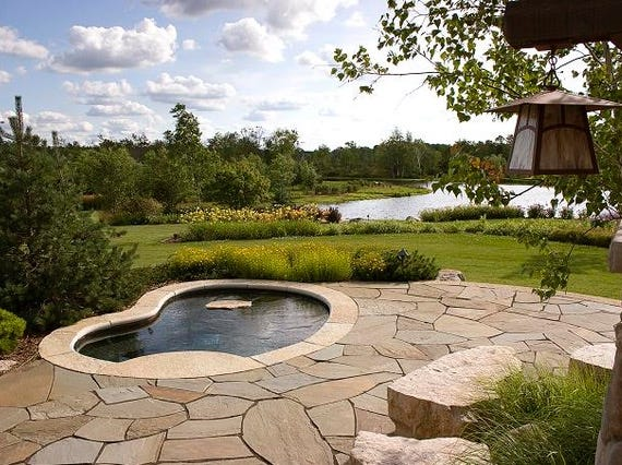 A patio that overlooks the water is accented at night by outdoor lighting that shines down onto the space.