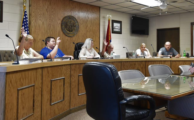 Cotter Mayor Peggy Hammack (center) asks the City Council for a show of hands in a vote on whether to accept a settlement in the city's lawsuit with Twin Lakes Recovery. Voting for the settlement are (from left, with arms raised) Carolyn Gill, Nathan Buck and Wayne Alexander while voting no are (from right) John Bell and Vikki Francis.