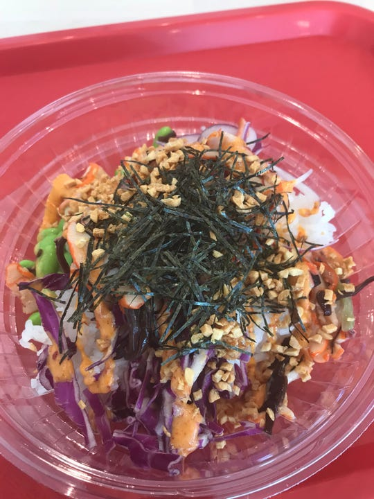 This Poke Fun build-your-own bowl has a sushi rice base, topped with ika (octopus/squid), sweet onion, red cabbage, edamame, crispy garlic, roasted seaweed and spicy mayo.