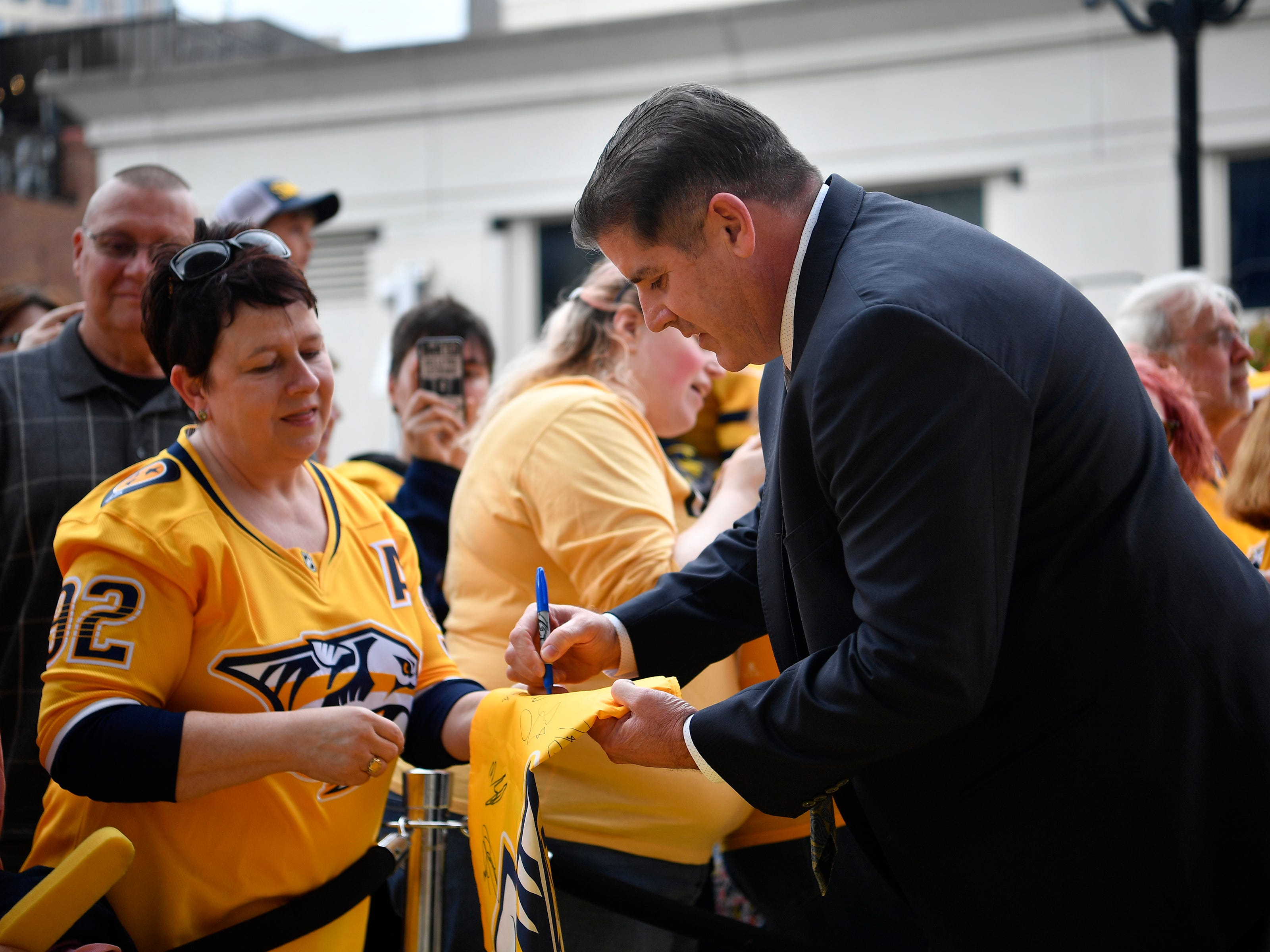 Predators head coach Peter Laviolette signs an autograph on the Gold Walk before the home opener at Bridgestone Arena in Nashville, Tenn., Tuesday, Oct. 9, 2018.